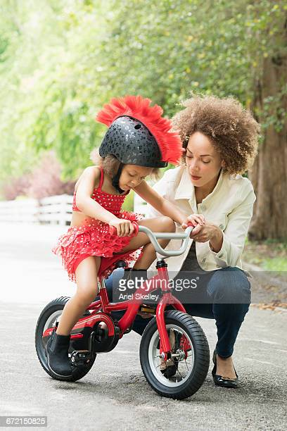 Mixed Race mother helping daughter with mohawk helmet on bicycle