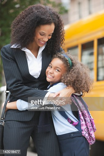 Mixed race mother hugging daughter near school bus : Stock Photo