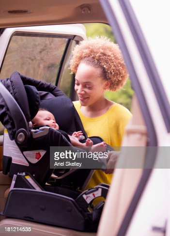 Mixed race mother loading baby into car seat
