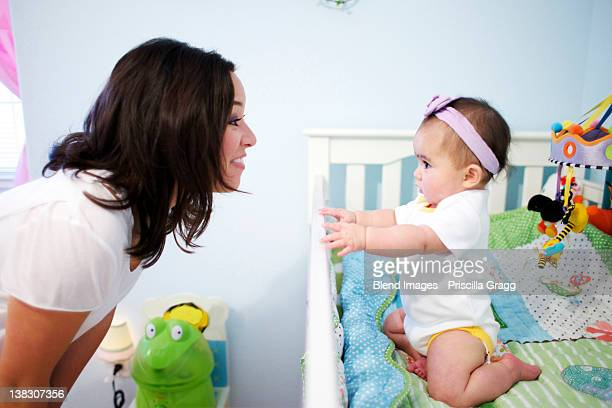 Mixed race mother looking at baby girl in crib