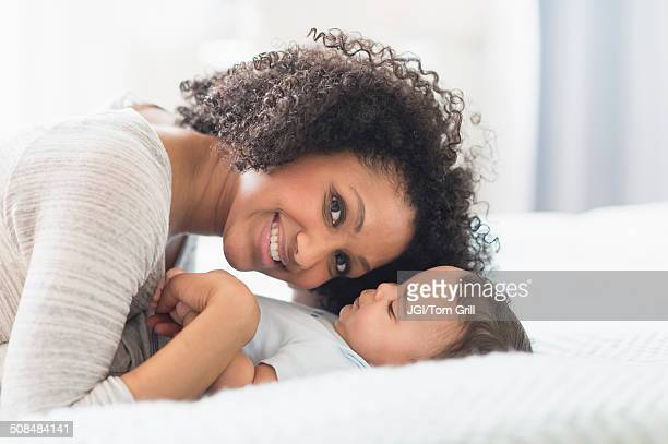 Mixed race mother playing with baby on bed