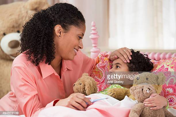 Mixed race mother taking daughter's temperature