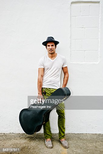 Mixed race musician carrying guitar case
