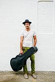 Mixed race musician carrying guitar case