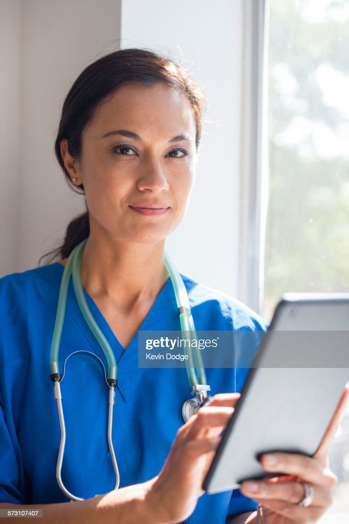 Mixed race nurse using digital tablet at window
