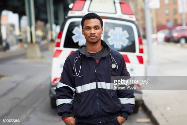 Mixed race paramedic standing near ambulance
