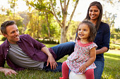 Mixed race parents and young daughter sit in park, close up