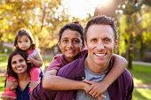 Mixed race parents carry kids piggyback, selective focus