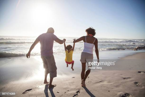 Mixed race parents lifting daughter on beach