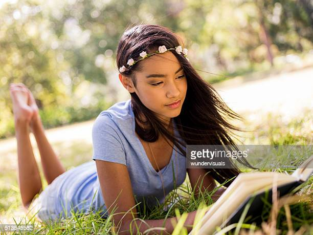 Mixed Race Person laying down outside reading a book