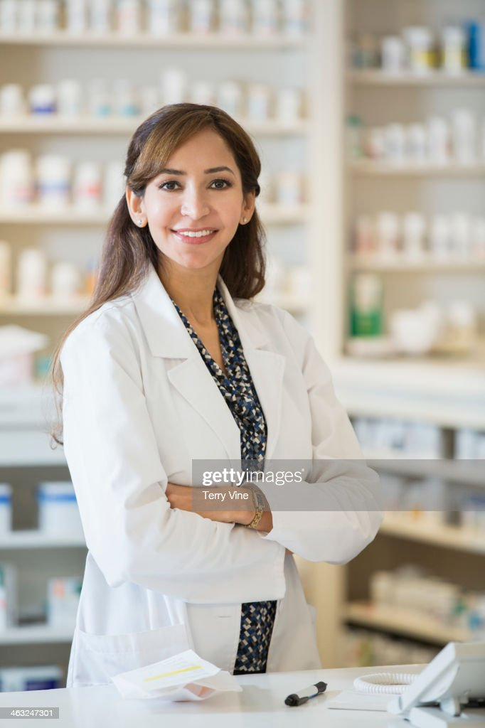 Mixed race pharmacist standing at counter : Stock Photo