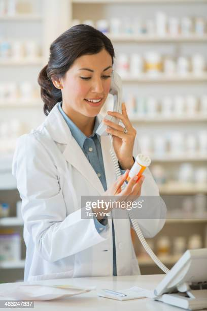 Mixed race pharmacist talking on telephone