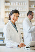 Mixed race pharmacist working at counter