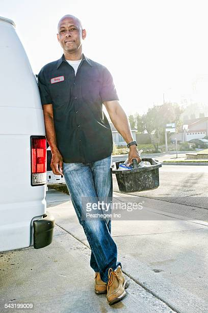 Mixed race plumber holding tools van