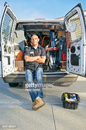 Mixed race plumber sitting in van
