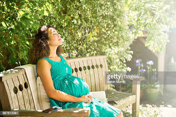 A mixed race pregnant lady relaxes in sunny garden