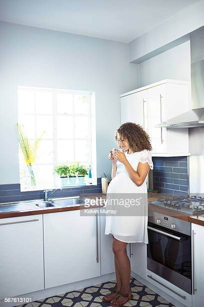 A mixed race pregnant lady stands in her kitchen