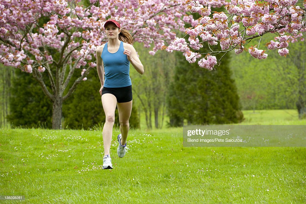 Mixed race runner jogging across field