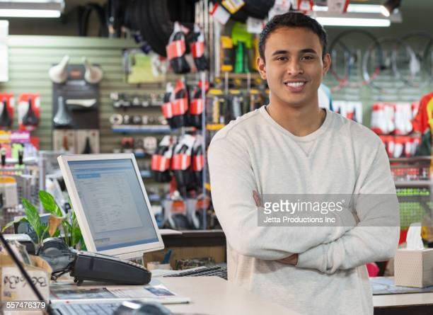 Mixed race salesman smiling in bicycle shop