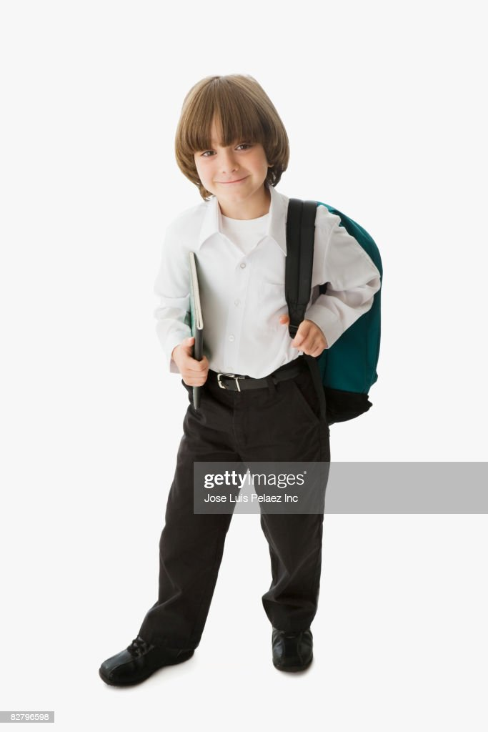 Mixed race school boy holding backpack and notebook : Stock Photo