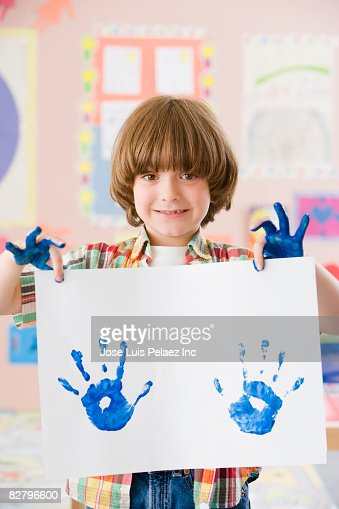 Mixed race school boy holding finger-painting : Stock Photo