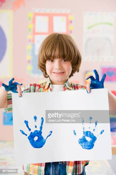 Mixed race school boy holding finger-painting