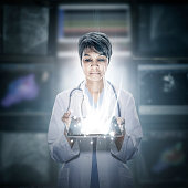 Mixed race scientist holding glowing digital tablet