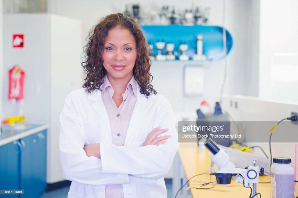 Mixed race scientist standing in laboratory : Stock Photo