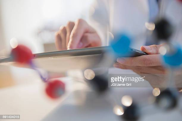 Mixed race scientist using digital tablet in laboratory