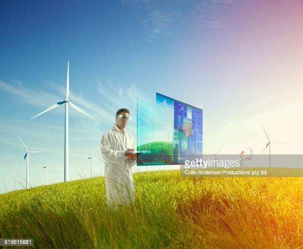 Mixed race scientist using holograph screen in field of wind turbines