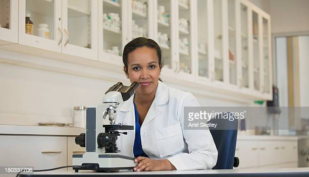 Mixed race scientist using microscope in laboratory
