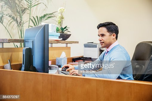 Mixed race secretary working in office lobby