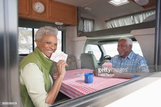 Mixed race Senior couple playing cards in RV