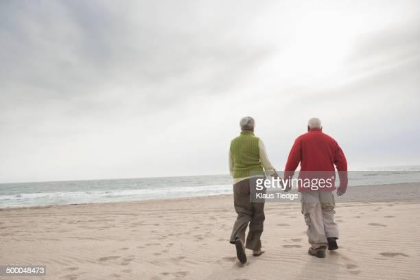 Mixed race Senior couple walking on beach