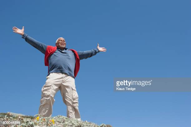 Mixed race Senior man cheering from cliff edge