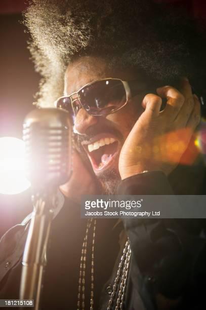Mixed race singer recording in studio