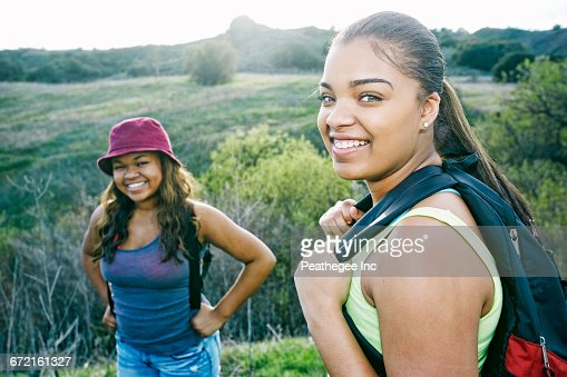Mixed Race sisters backpacking in field