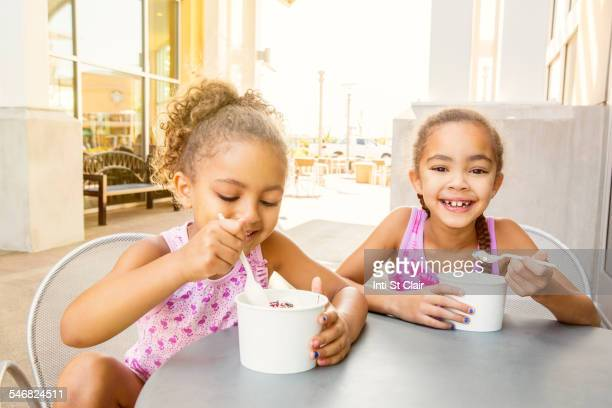 Mixed race sisters eating ice cream at outdoor cafe
