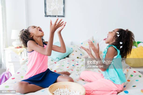 Mixed race sisters eating popcorn on bed