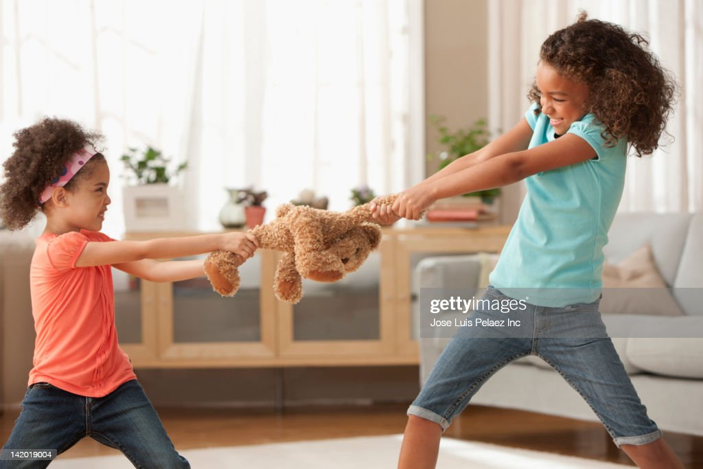 Mixed race sisters fighting over teddy bear