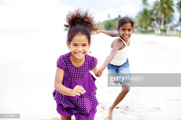 Mixed race sisters holding hands running on beach