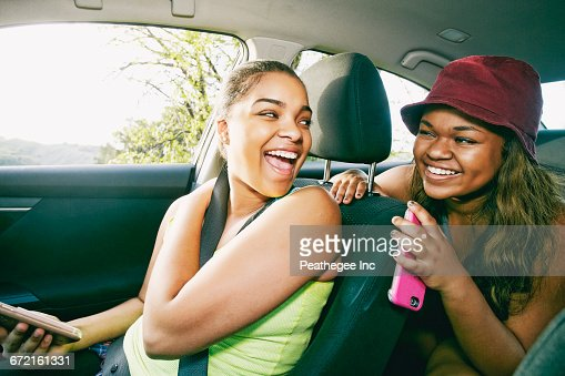 Mixed Race sisters laughing in car