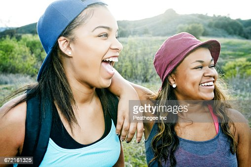 Mixed Race sisters laughing in field