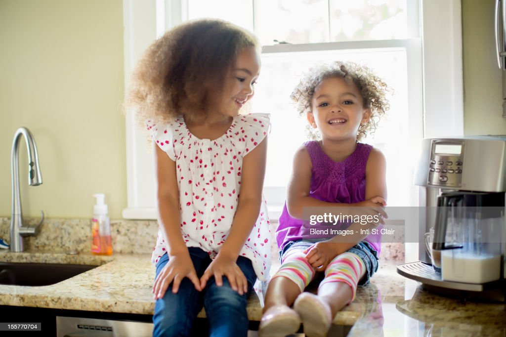 Mixed race sisters sitting on kitchen counter : Stock Photo