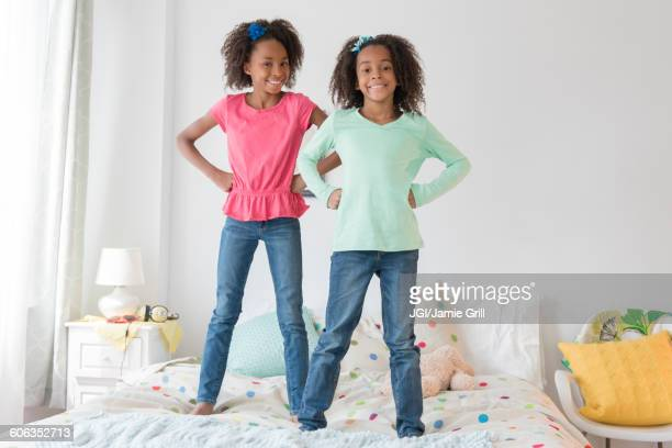 Mixed race sisters standing on bed