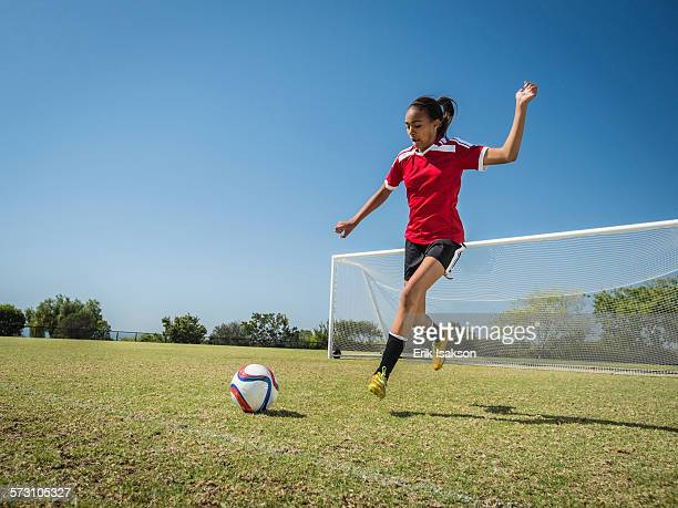 Mixed race soccer player kicking ball on field