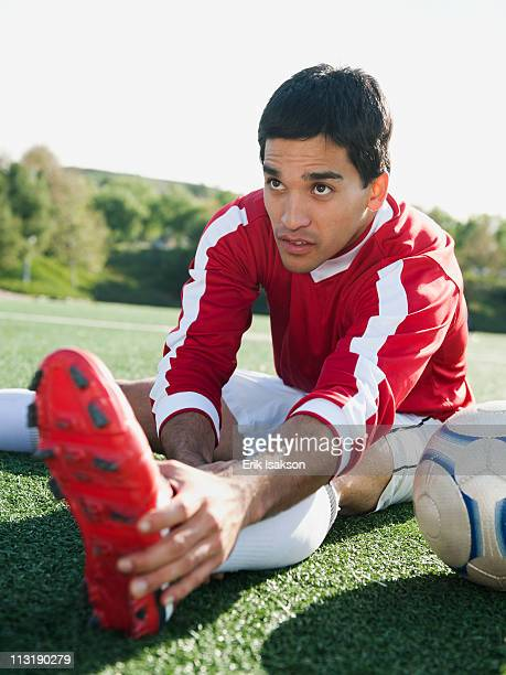Mixed race soccer player stretching