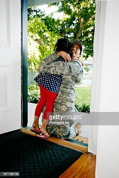 Mixed race soldier mother hugging daughter in front door