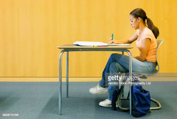 Mixed race student doing homework in library