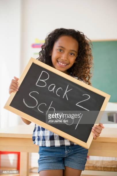Mixed race student holding blackboard reading back 2 school